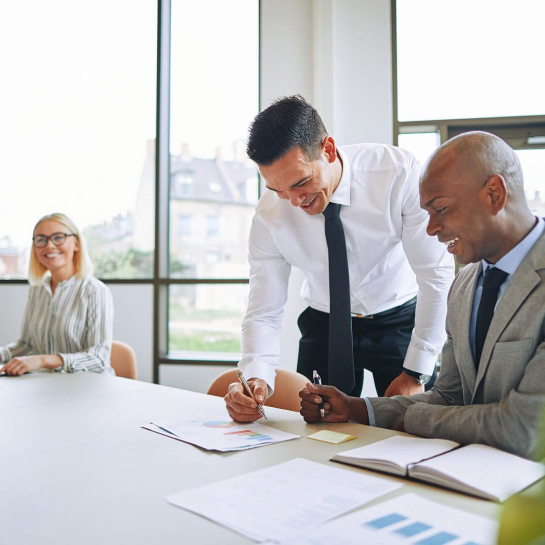 two-smiling-businessmen-discussing-paperwork-7YPYP9Q-1.jpg