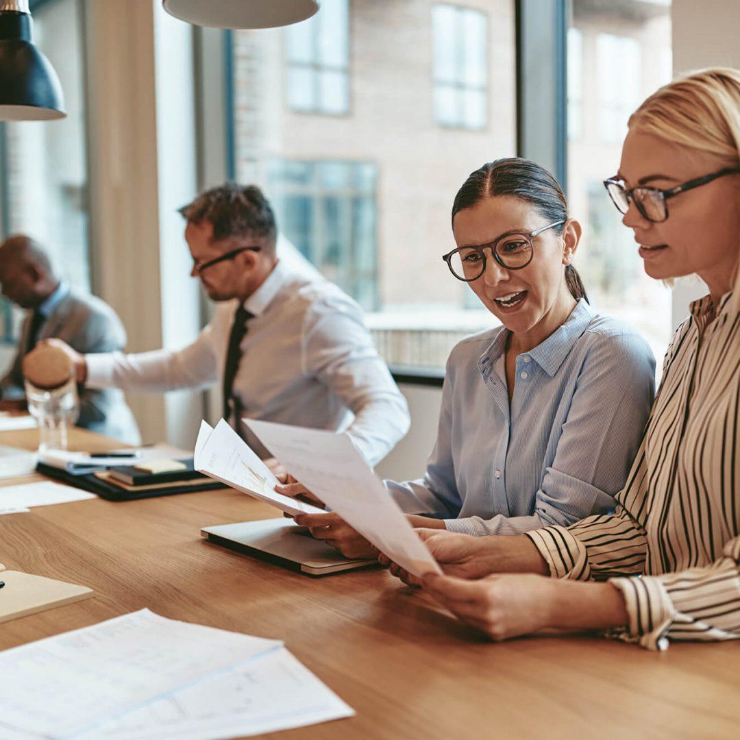 two-smiling-businesswomen-going-over-paperwork-at-LLDYSYA-1.jpg